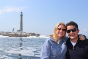 On a boat with lighthouse in the back