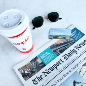 Coffee, a room key, sunglasses and the newport daily news