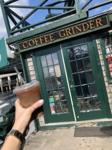 Iced coffee in front of coffee grinder